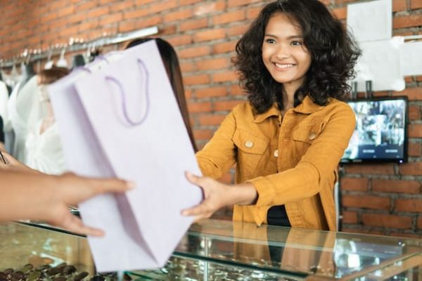 attractive woman asian shop keeper giving shopping bag to customer